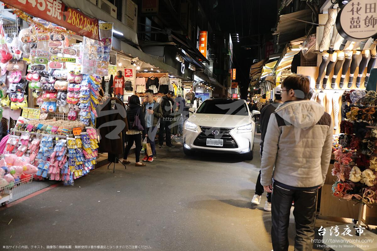 士林夜市の中を通過する車