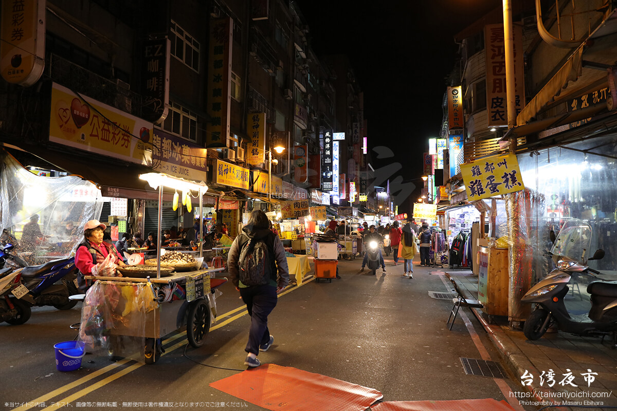 廣州街夜市の中を通過するバイク