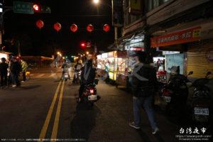 夜市の中を走るバイク