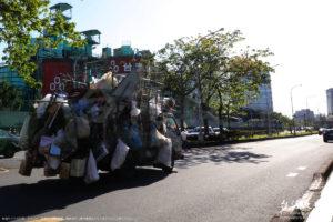 トラックの荷台に積まれた缶やビニール袋が地面スレスレ